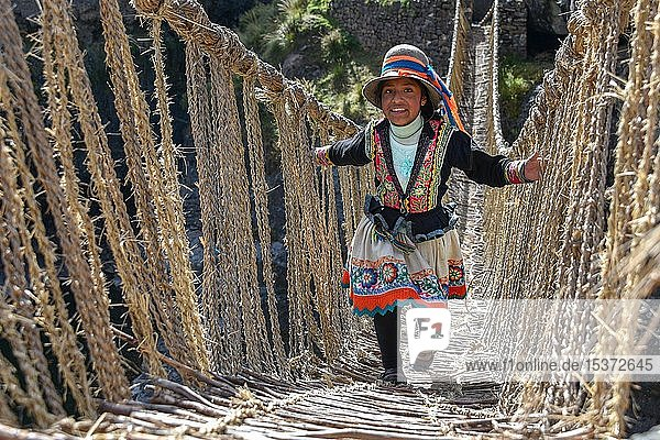 Laughing local girl in traditional costume walks over Inca suspension bridge Q'iswachaka  rope bridge made of braided Ichu grass over the river Apurimac  province Canas  Peru  South America