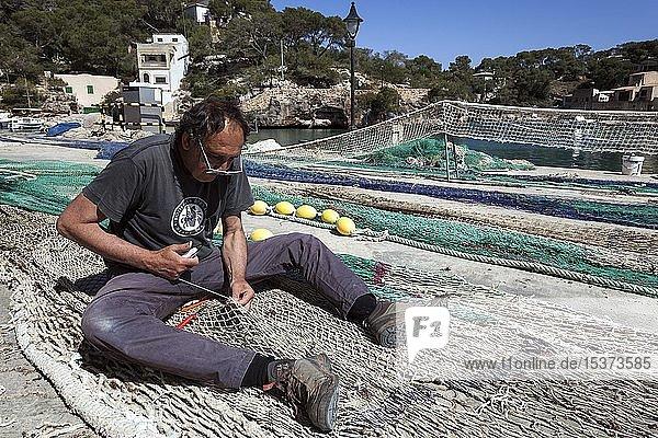 Fischer repariert Fischernetze im Hafen von Cala Figuera  Mallorca  Balearen  Spanien  Europa