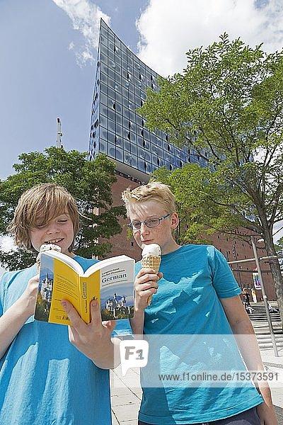 Jugendliche auf Sprachreise studieren ein Wörterbuch vor der Elbphilharmonie  Hamburg  Deutschland  Europa