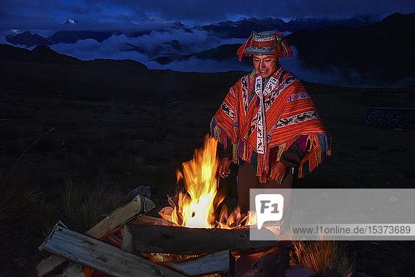 Indio man with hat and colorful traditional poncho standing at a campfire in the Andes  near Cusco  Peru  South America