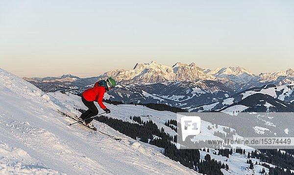 Skifahrerin auf der Skipiste an steiler Abfahrt  hinten Berge  SkiWelt Wilder Kaiser  Brixen im Thale  Tirol  Österreich  Europa