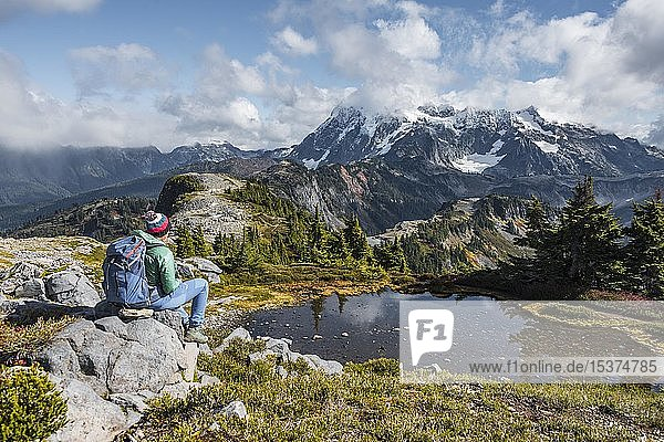 Female hiker resting on a rock at a small mountain lake  view from Tabletop Mountain to Mt. Shuksan with snow and glacier  Mt. Baker-Snoqualmie National Forest  Washington  USA  North America