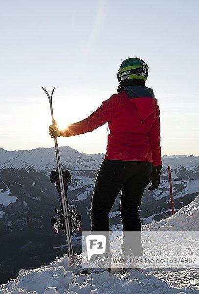 Skifahrerin mit Skihelm steht mit Ski an der Skipiste  blickt in die Ferne  hinten Berge  SkiWelt Wilder Kaiser  Brixen im Thale  Tirol  Österreich  Europa