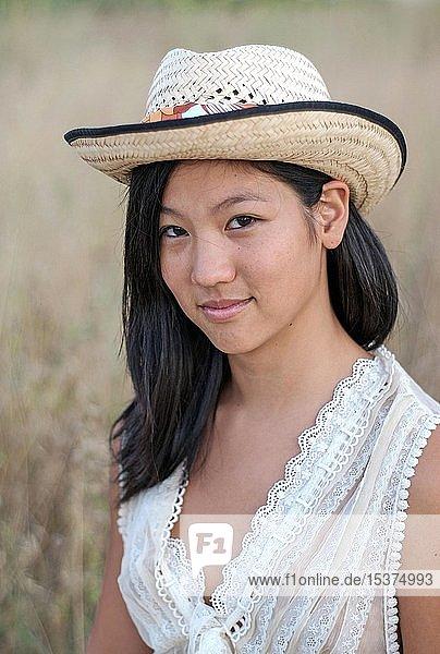 Junge Asiatin mit Sonnenhut in der Natur  Portrait  Ibiza  Spanien  Europa