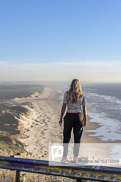 Junge Frau blickt in die Ferne an einem Aussichtspunkt  Blick über den Baker Beach  Oregon Coast Highway  Oregon  USA  Nordamerika