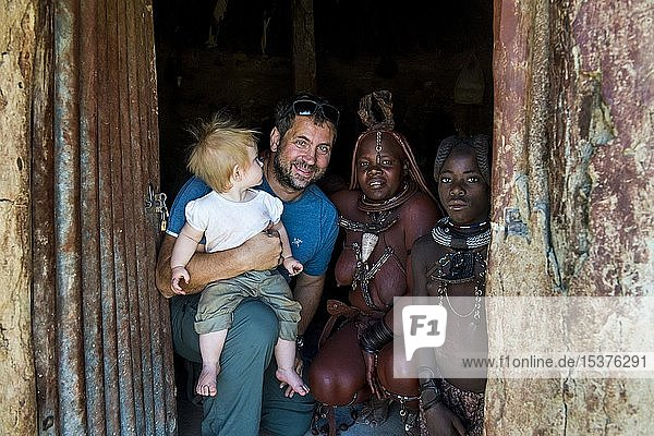 Weißer Tourist mit seinem Baby in einem Himba-Dorf mit Himba-Leuten  Kaokoland  Namibia  Afrika