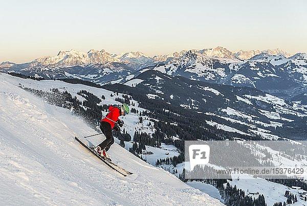 Female skier skiing steep downhill  black piste  behind mountains  Brixen im Thale  Tyrol  Austria  Europe