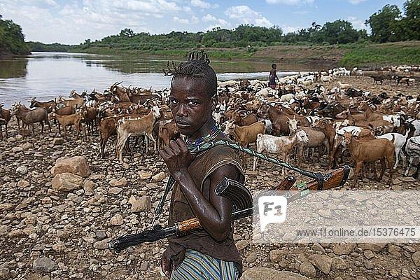 Ziegenhirte vom Volksstamm der Hamer mit Kalaschnikow  bewacht Ziegenherde am Omo Fluss  Murulle  Unteres Omo-Tal  Omo-Region  Süd-Äthiopien  Äthiopien  Afrika