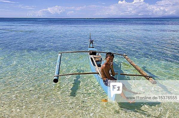 Junger Filipino sitzt auf kleinem Auslegerboot am Bounty Beach  Malapascua  Cebu  Philippinen  Asien