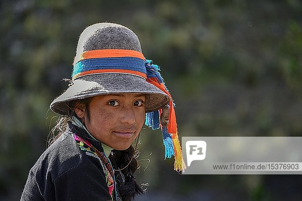 Indio girl with hat with colorful ribbons smiles  portrait  by Cusco  Peru  South America