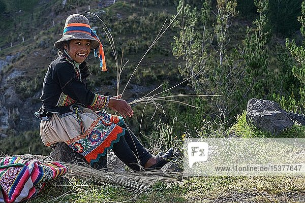 Indio girl with hat smiles and weaves Pacha grass  near Cusco  Peru  South America
