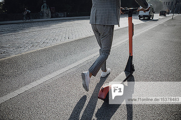 Businessman walking with e-scooter in the city