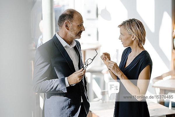 Geschäftsmann und -frau im Gespräch über Lösungen
