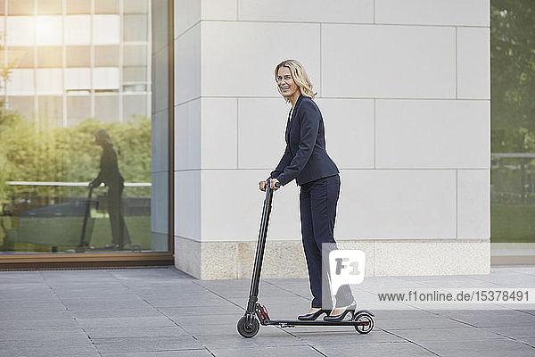 Geschäftsfrau auf E-Scooter fährt an Bürogebäude in der Stadt vorbei