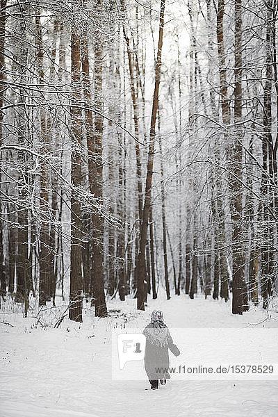 Back view of little girl wearing headscarf walking in winter forest