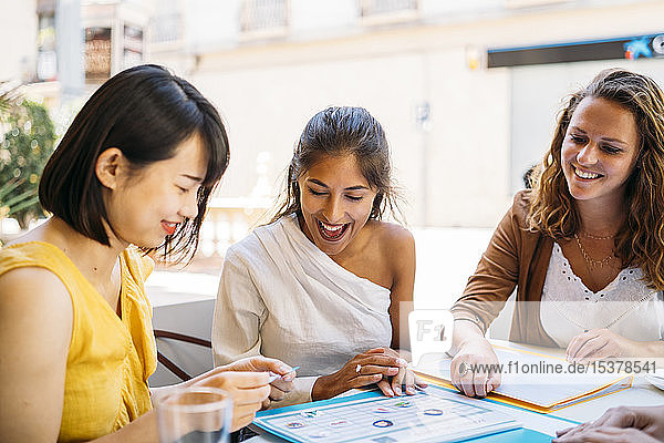 Happy female multicultural students meeting in a cafe organizing their class schedule