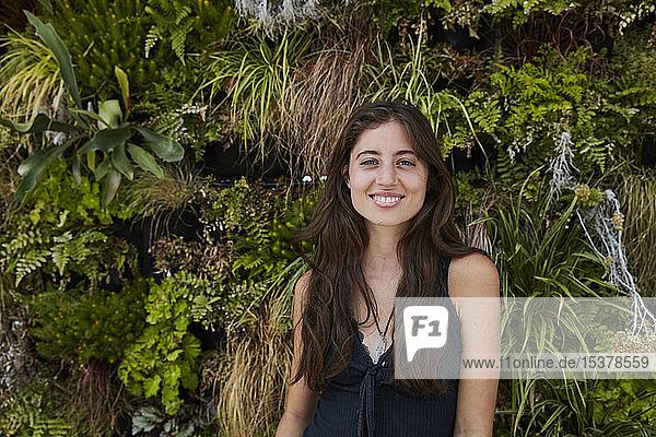 Porträt einer lächelnden jungen Frau vor einer Pflanzenwand
