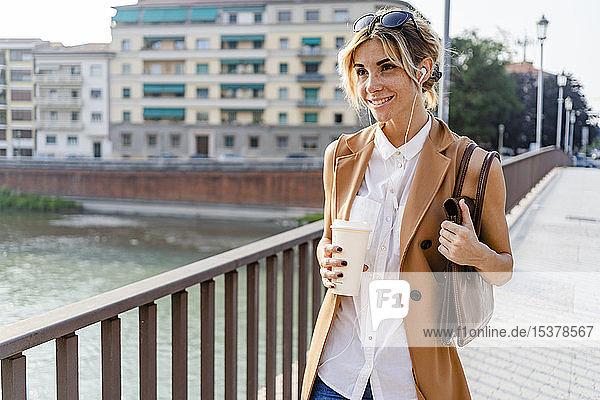 Lächelnde Frau mit Kopfhörern und Kaffee zum Stadtbummel