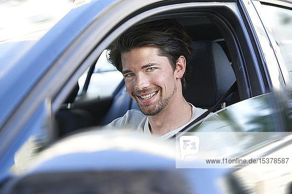Porträt eines lächelnden Mannes beim Autofahren