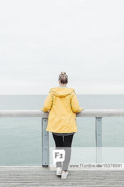 Rückansicht einer jungen Frau in gelbem Regenmantel
