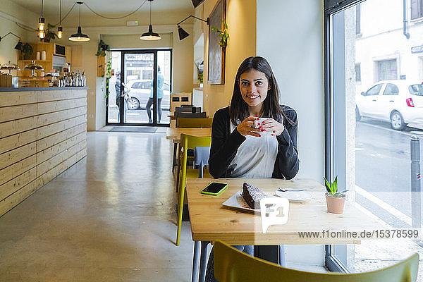 Porträt einer lächelnden jungen Frau  die in einem Cafe sitzt