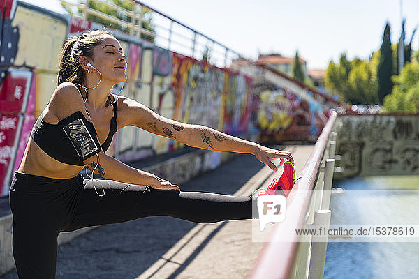 Young woman stretching on a bridge