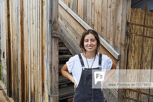 Porträt einer lächelnden jungen Frau vor einem Holzzaun