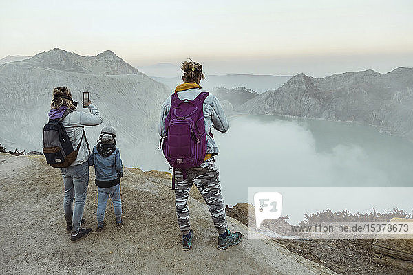 Family with respirator masks standing at the edge of volcano Ijen  Java  Indonesia