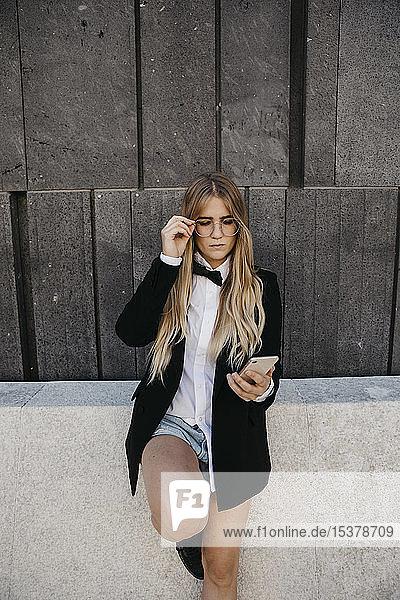 Porträt einer blonden jungen Frau mit schwarzer Krawatte und Blazer  die auf ihr Handy schaut  Wien  Österreich