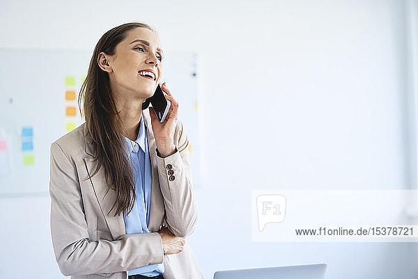 Fröhliche Geschäftsfrau telefoniert im Büro