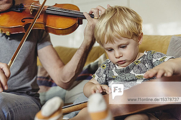 Portrait of toddler testing ukulele while his father playing violin