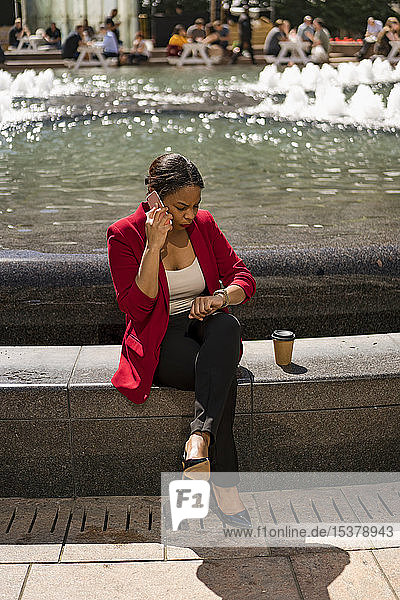Businesswoman on the phone checking the time  London  UK