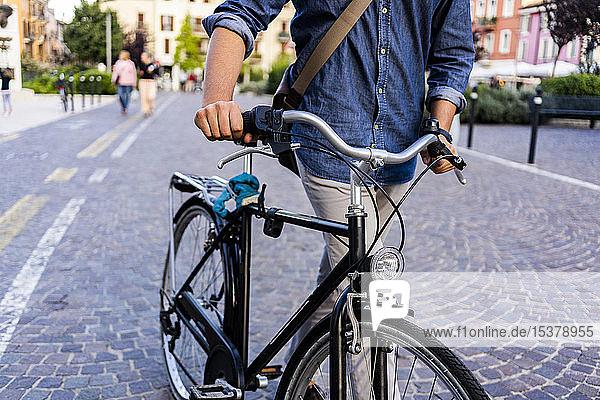 Mann  der in der Stadt ein Fahrrad schiebt