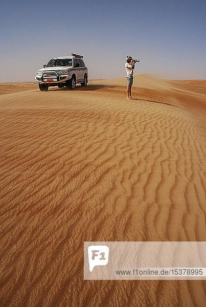Mann beim Fotografieren in der Wüste  neben einem Geländewagen  Wahiba Sands  Oman