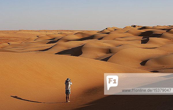 Mann beim Fotografieren in der Wüste,  Wahiba Sands,  Oman