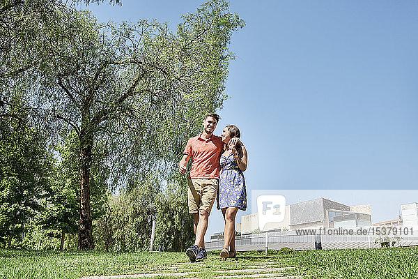 Glückliches junges Paar beim Spaziergang durch einen Park