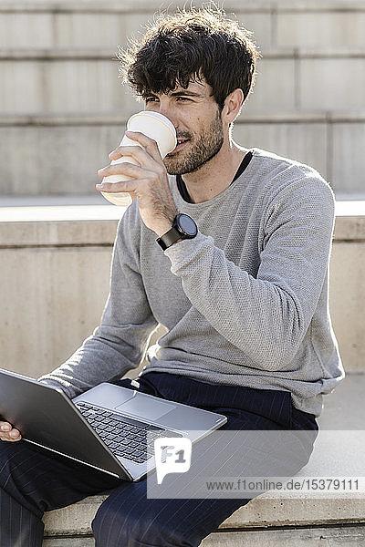 Mann sitzt auf einer Außentreppe mit Kaffee zum Mitnehmen und Laptop