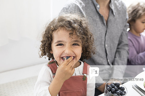 Porträt eines verspielten Jungen  der mit seiner Familie bei Tisch Blaubeeren isst