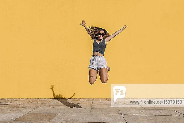 Glückliche junge Frau springt vor eine gelbe Mauer