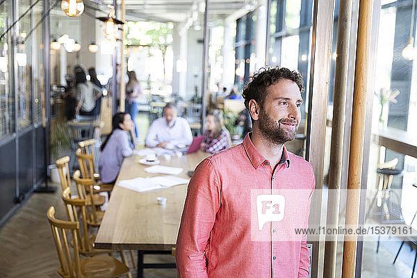 Porträt eines Gelegenheits-Geschäftsmannes in einem Cafe mit Kollegen,  die im Hintergrund ein Treffen haben