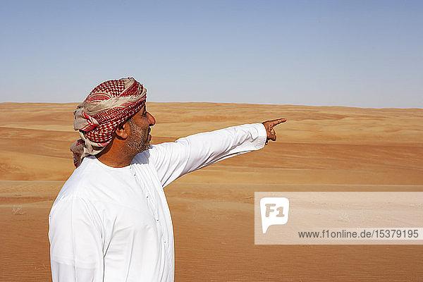Beduine in Nationaltracht in der Wüste stehend  auf Distanz zeigend  Wahiba Sands  Oman