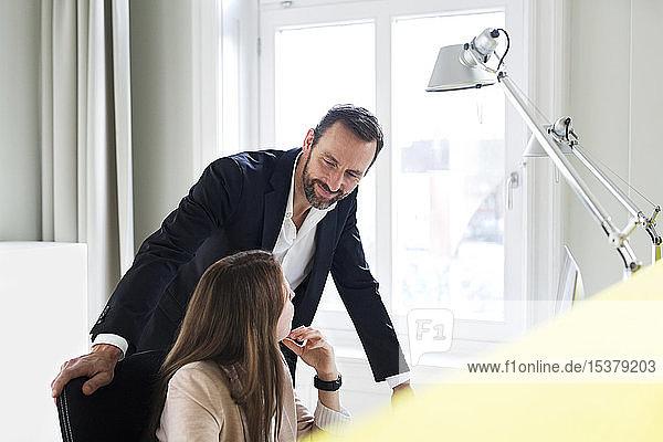 Geschäftsmann und Angestellter sprechen am Schreibtisch im Büro