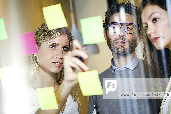 Three business people brainstorming together with sticky notes on a glass wall