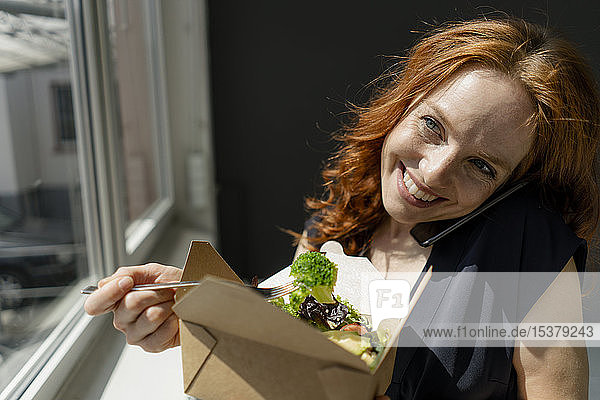 Portrait of happy redheaded businesswoman eating healthy takeaway food and talking on the phone