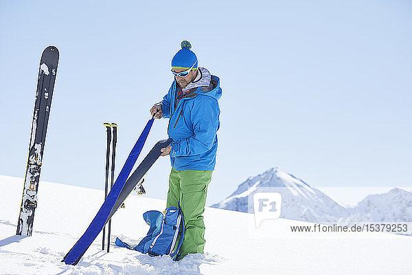 Ski tourer attaching pelt to ski in the mountains  Kuehtai  Tyrol  Austria