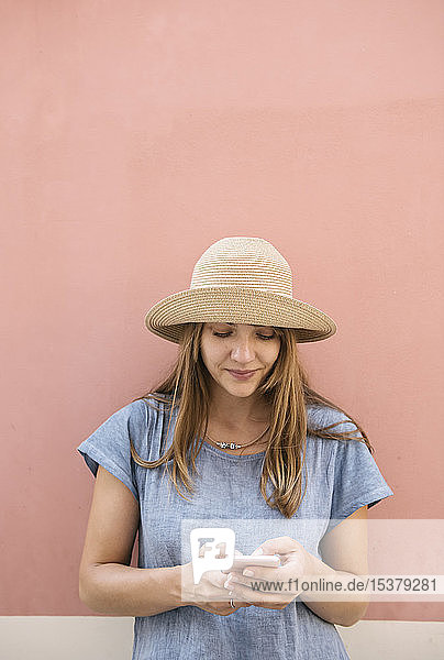 Frau steht mit einem Smartphone an einer rosa Wand