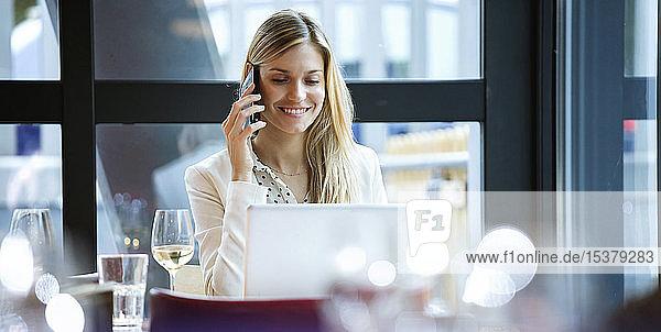 Lächelnde Geschäftsfrau mit Handy und Laptop in einem Restaurant