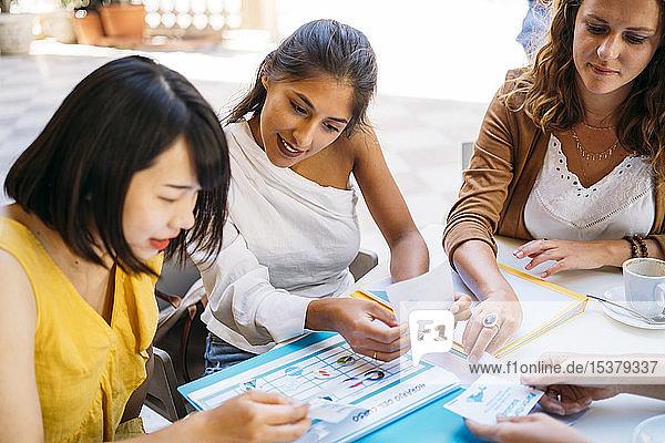 Weibliche multikulturelle Studentinnen treffen sich in einem Café und organisieren ihren Stundenplan
