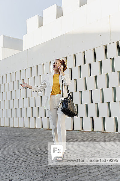 Businesswoman in white pant suit  walking in the city  talking on the phone