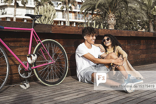 Young couple with bicycle sitting in the city  talking